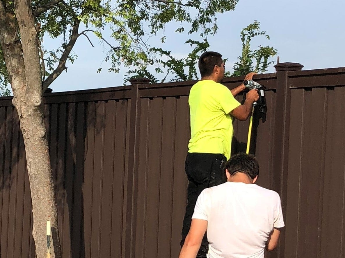 Fence installer using finish nail gun to secure trex fence pickets.