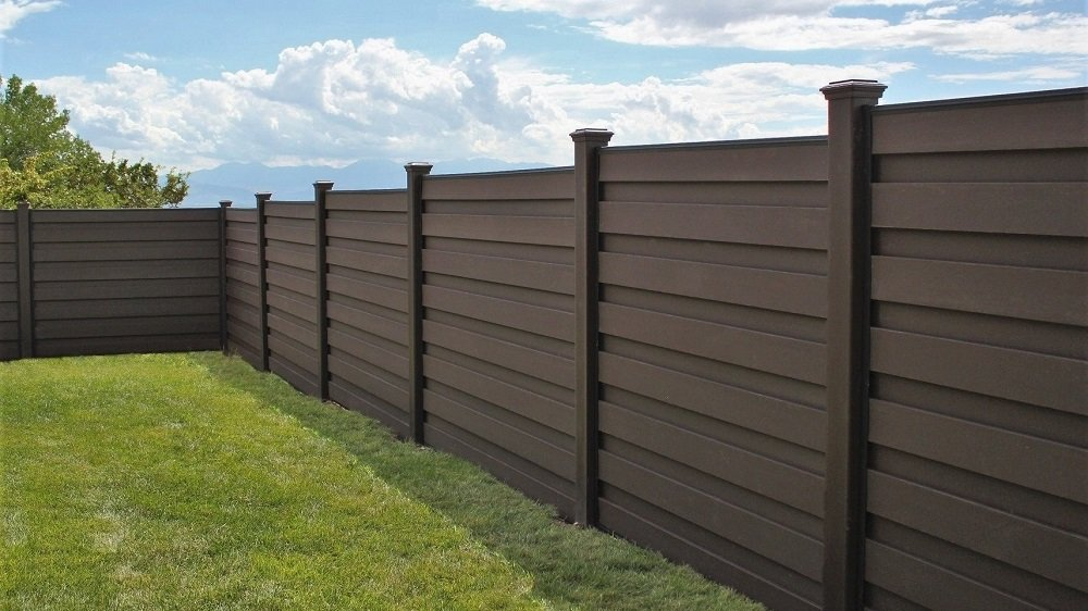 A Trex horizontal fence stepping with sloping ground down a hill
