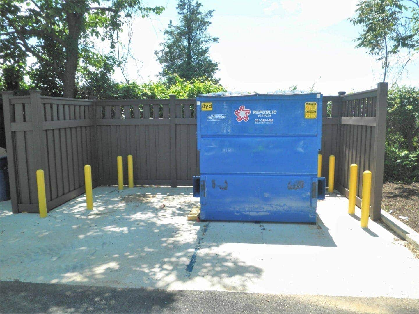 A dumpster in a trash enclosure made from Trex Fencing