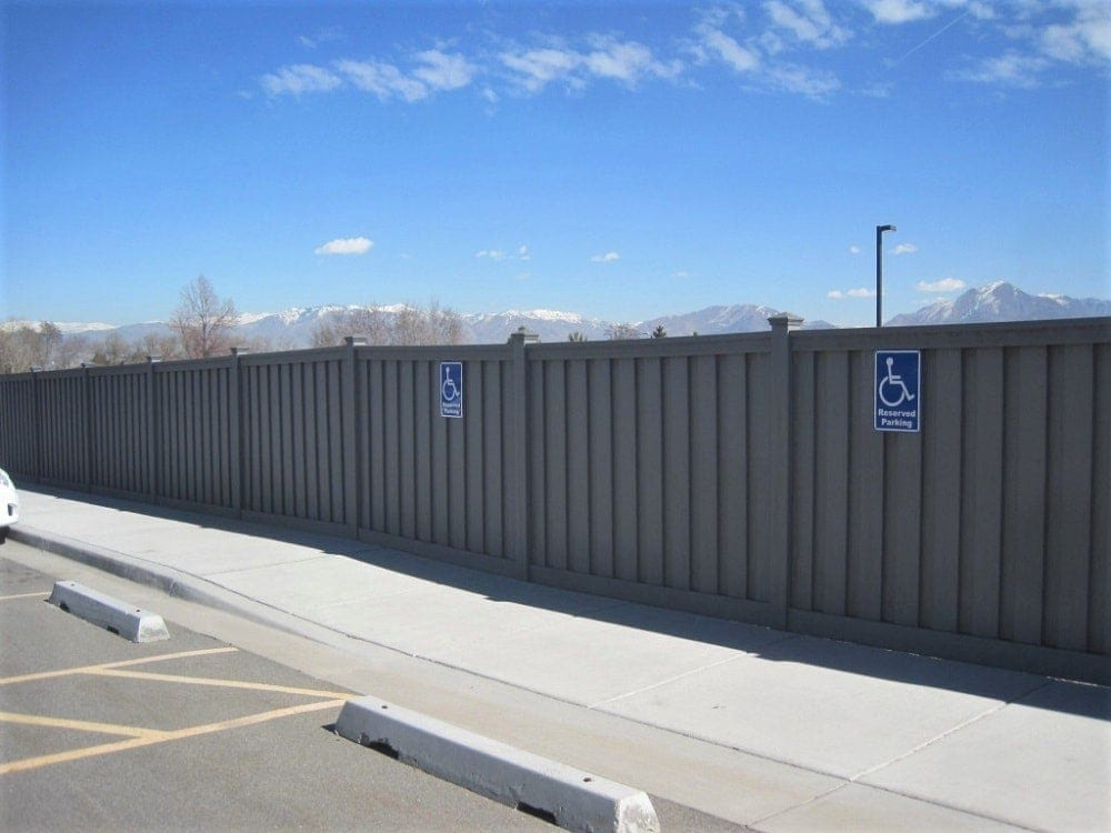 A Trex fence running along a sidewalk in the Nelson Labs parking lot.