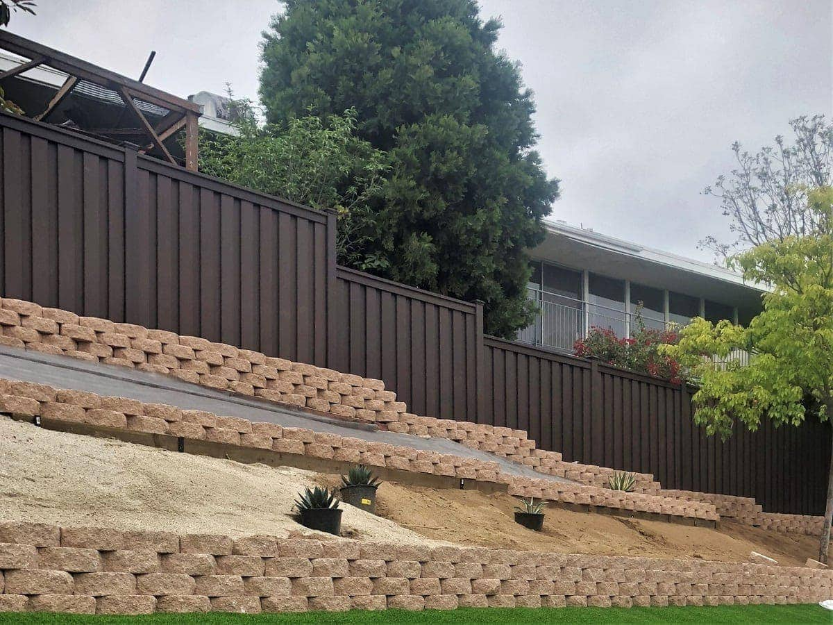 A Woodland Brown Trex Fence above tiered retaining walls in Southern California backyard