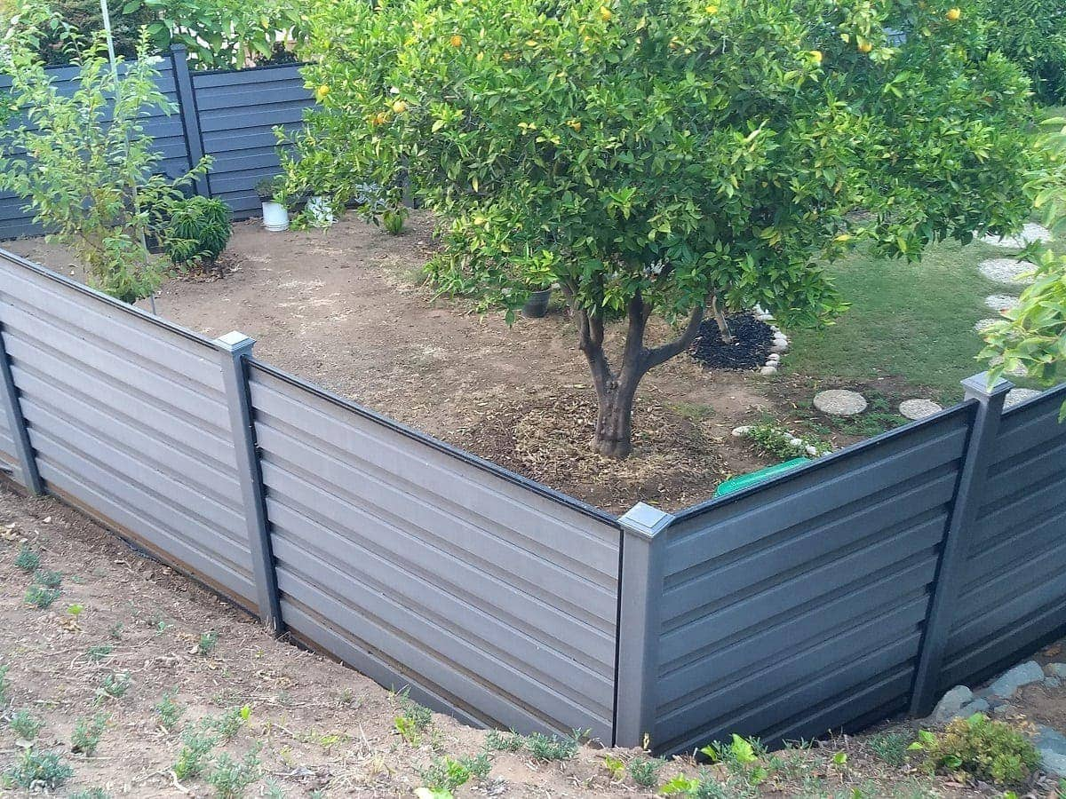 A Winchester Grey Trex Horizons horizontal fence enclosing a Southern California backyard with orange trees.