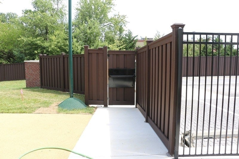 A Trex Fence with a gate. The gate has a panic bar panel to allow restricted access into the school property.