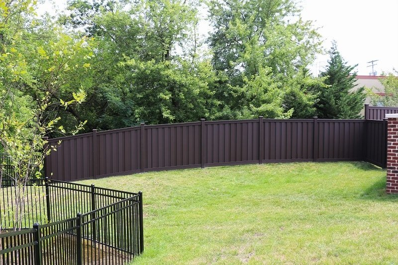 A Trex Fence at the back of the sloping grassy play area at the Goddard School