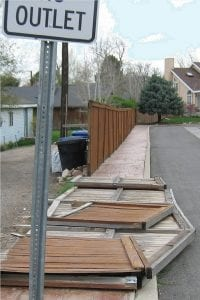 Damaged wood fence. Posts have rotted and the fence panels are lying on the ground.