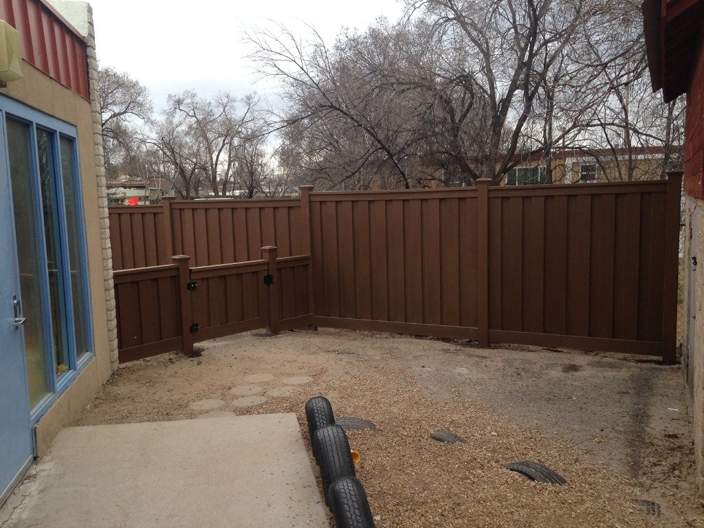 A small Trex gate and fence separating play areas in an early childhood development center's backyard.