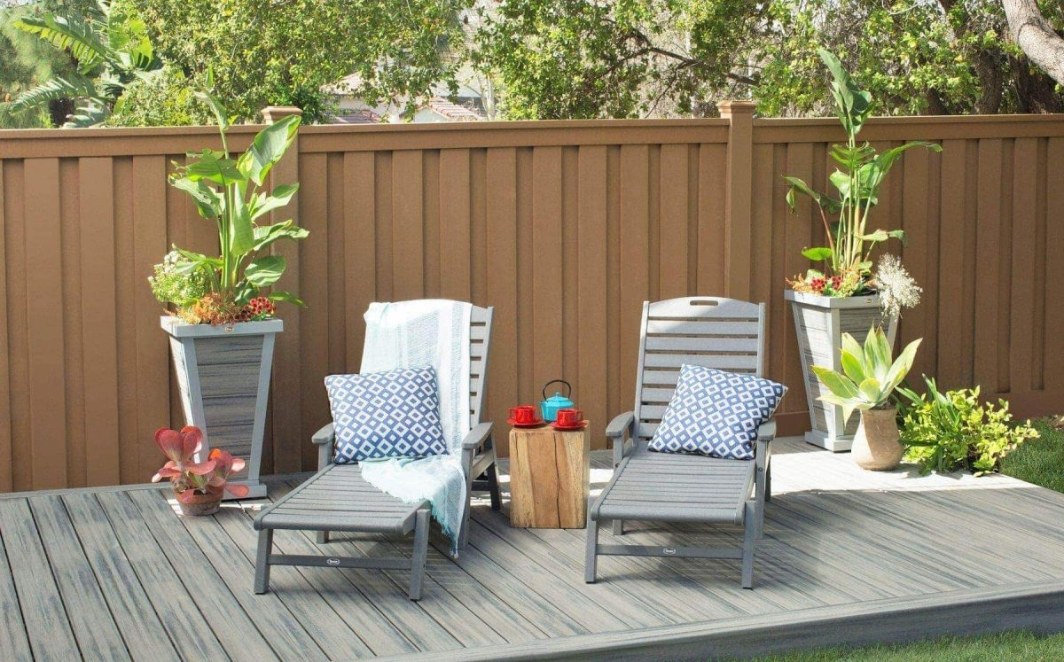 A fully private Trex fence in front of a Trex deck with lawn chairs