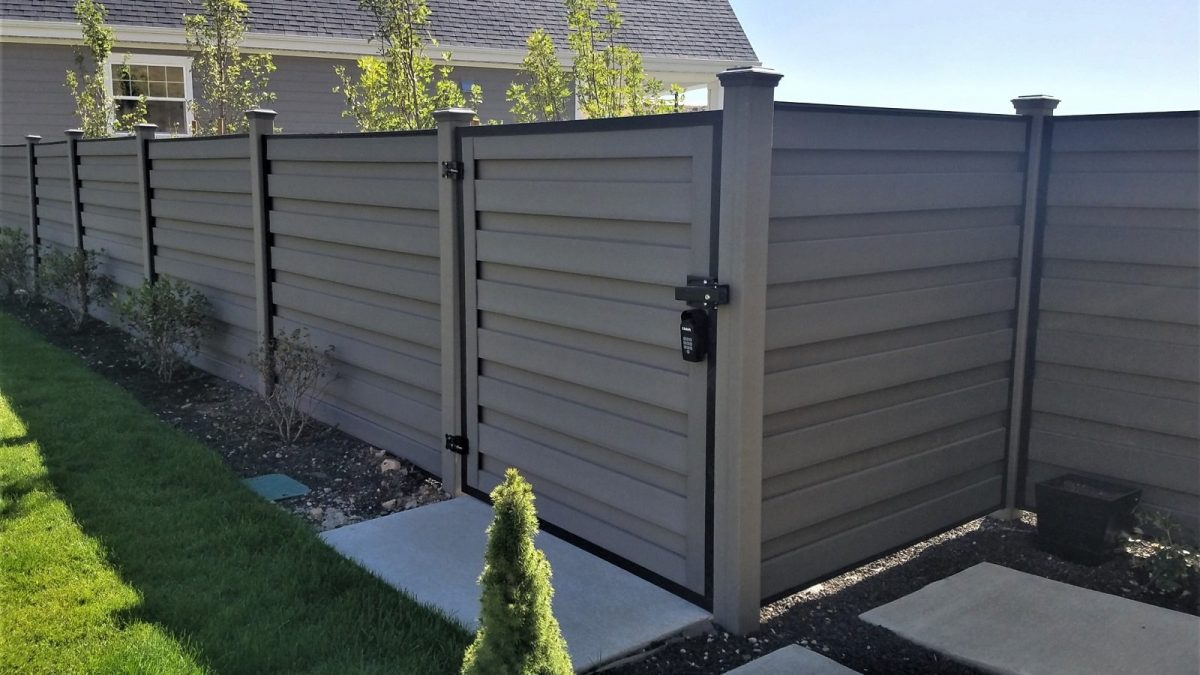 A horizontal fence made from Trex Winchester Grey composite fencing and Horizons horizontal black steel fence frames in a landscaped yard.