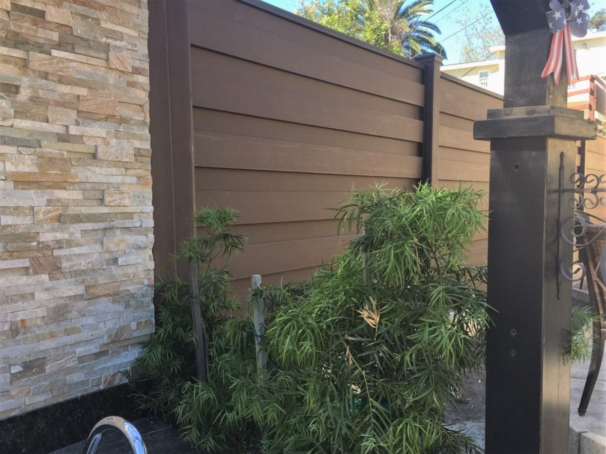 A Trex fence with the Horizons horizontal system next to a textured rock wall.