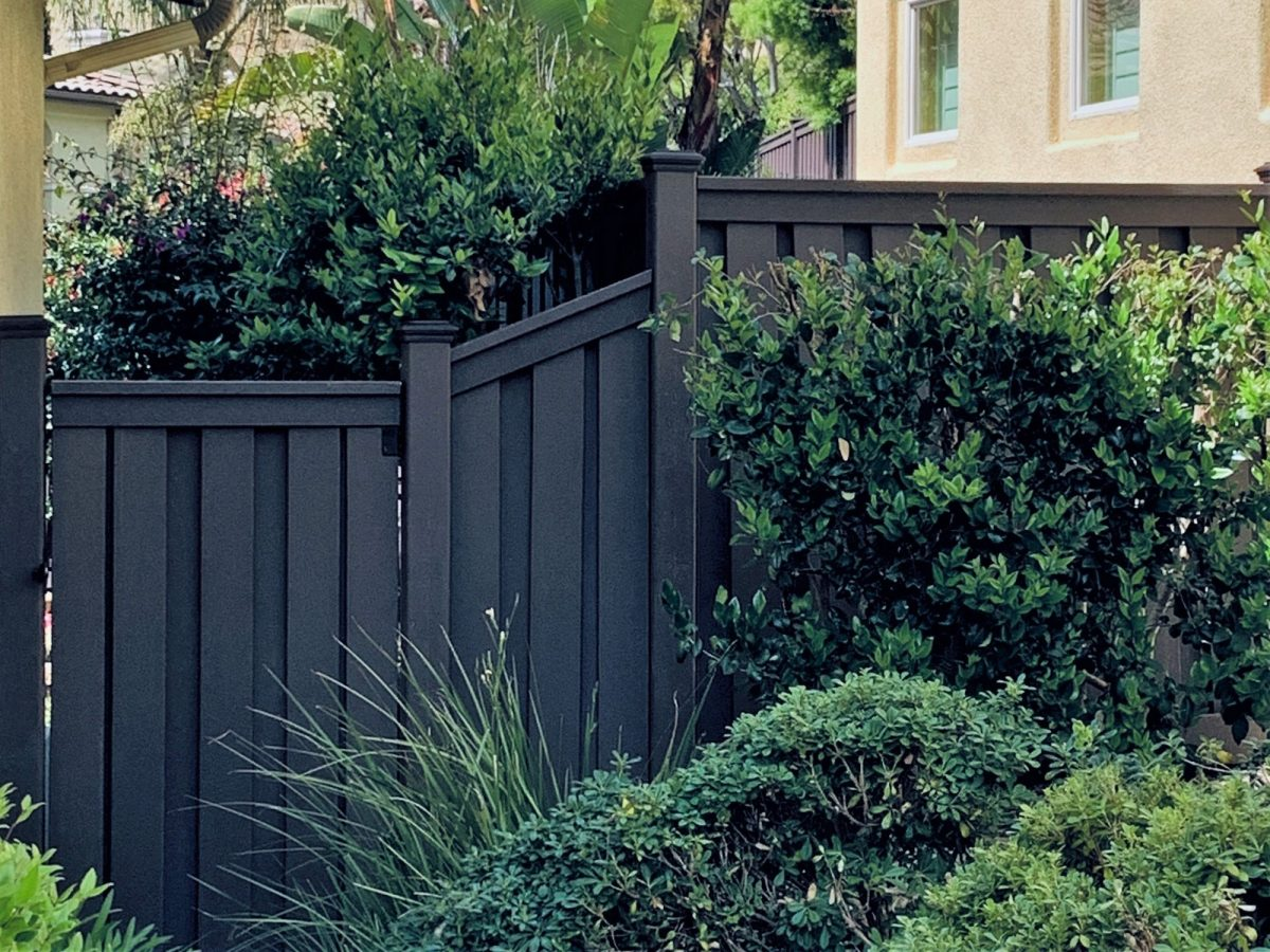A Trex gate with a sloped section next to it closing off a backyard.