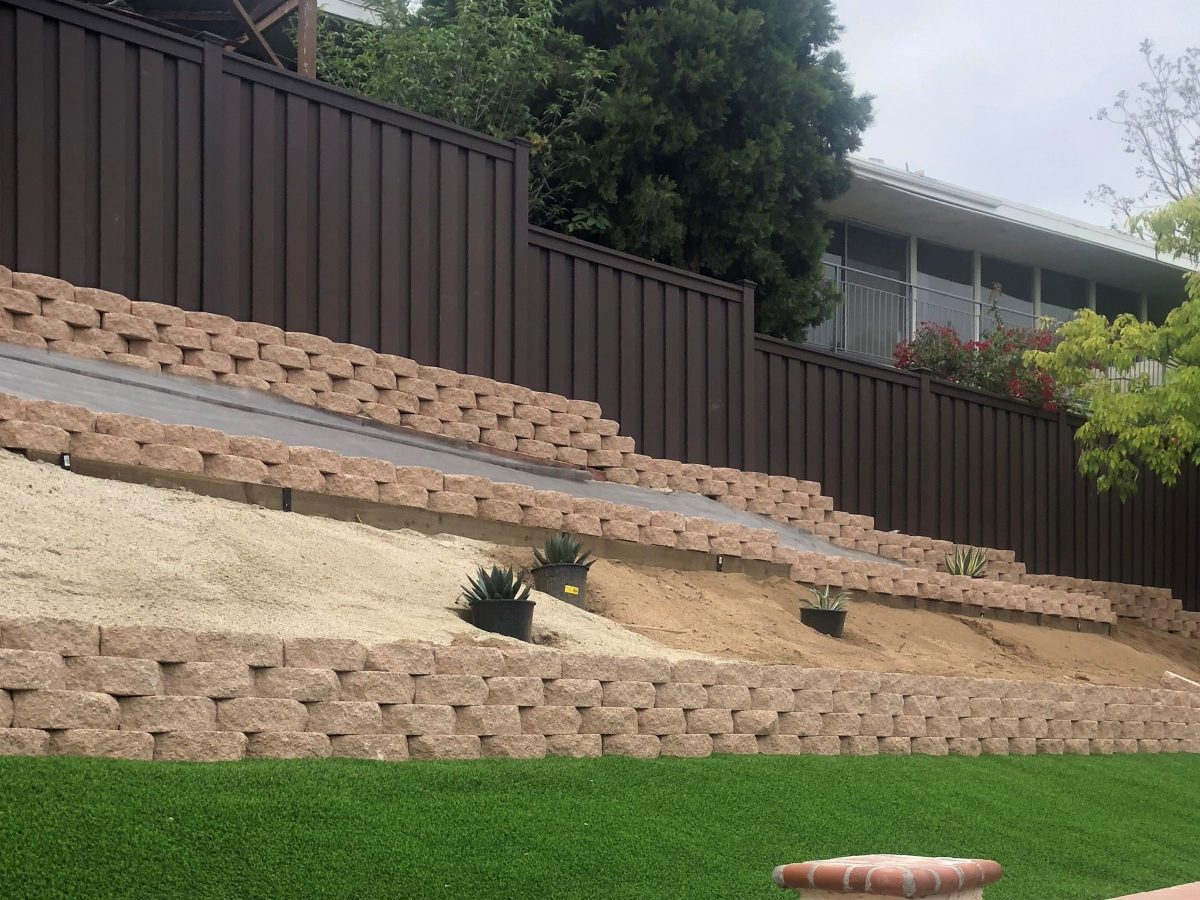 A Trex Fencing providing a backdrop to a terraced backyard. The terraced walls are made from landscaping blocks.