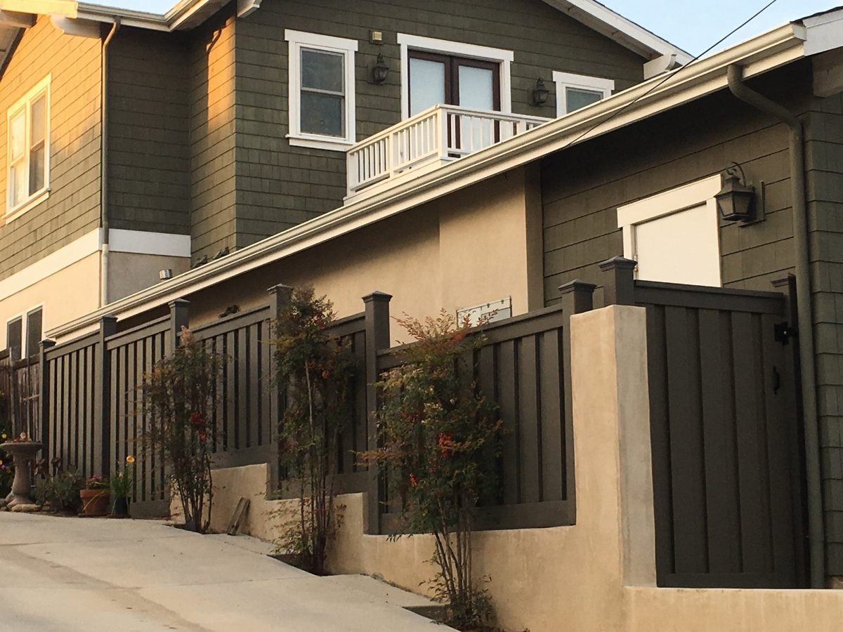 Trex Fencing panels mounted on top of a stucco wall next to a driveway. The fence stair steps up the wall.