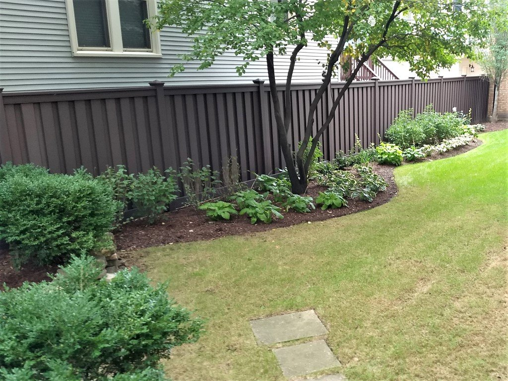 A landscaped backyard with Trex Fencing Woodland Brown 6' tall privacy fencing
