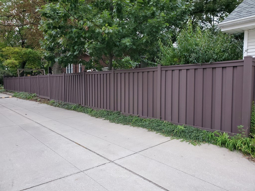 A Woodland Brown Trex Fence along a paved alley in Chicago