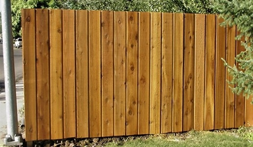 A wood fence with pickets overlapping to create a board-on-board look.